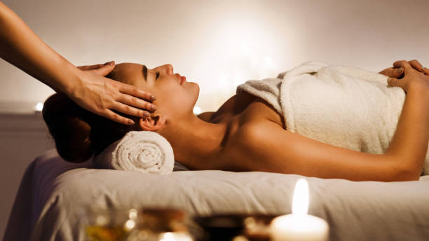 Young woman enjoying face massage in spa salon Young woman enjoying face massage with aromatic candles in spa salon massaging stock pictures, royalty-free photos & images