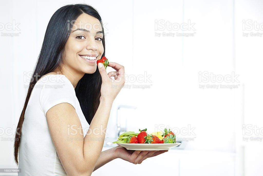 Young woman enjoying fruit salad stock photo