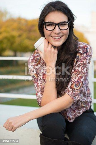 istock Young woman enjoying her coffee to go 495471534