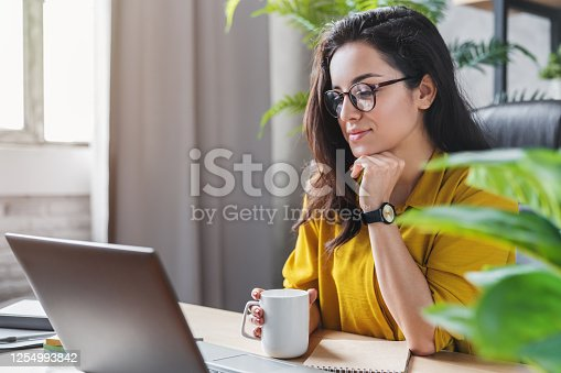Young woman enjoying her coffee while working or studying on laptop computer at home office