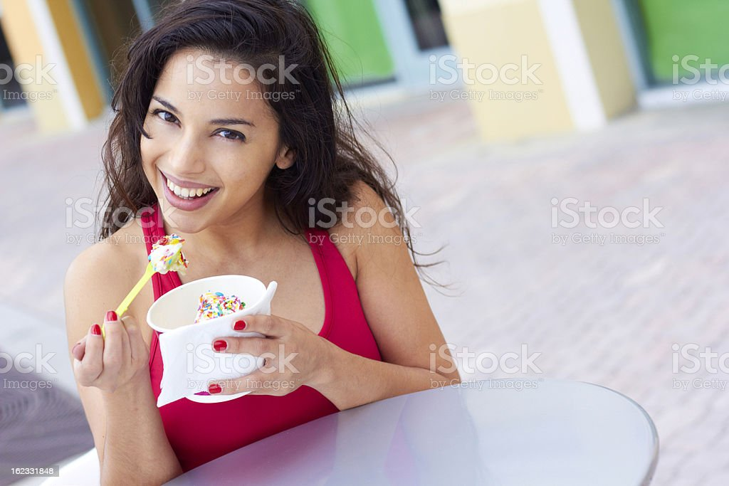 A young woman enjoying her frozen yogurt with sprinkles stock photo