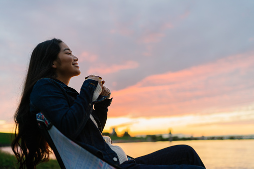 A young woman is enjoying sitting near a lake and drinking a hot drink in nature during sunset.