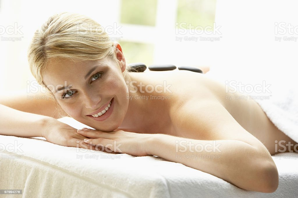 Young Woman Enjoying Hot Stone Treatment royalty free stockfoto