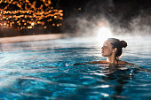 Beautiful woman swimming in a swimming pool with steam.