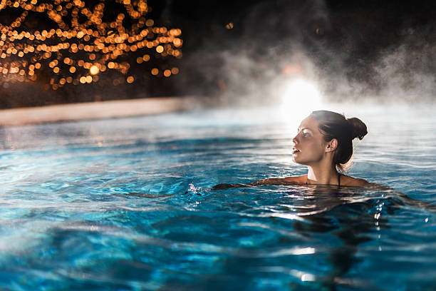 young woman enjoying in a heated swimming pool at night. - hot spring stock photos and pictures