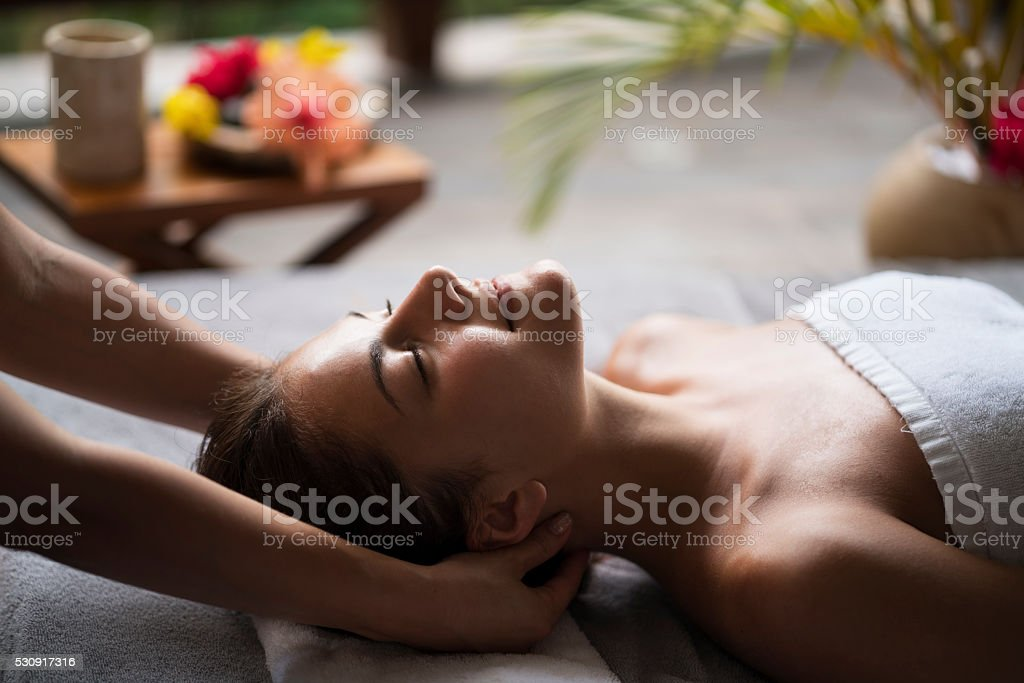 Young woman enjoying in a neck massage at the spa. stock photo