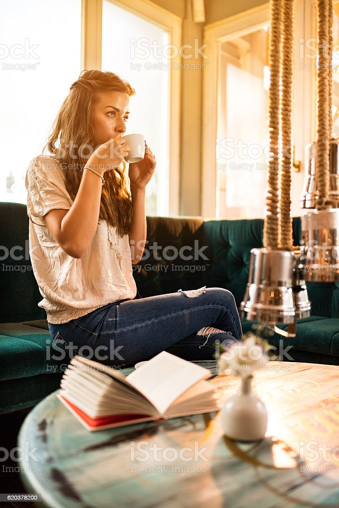 Young woman enjoying in cup of coffee at home. zbiór zdjęć royalty-free