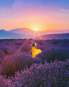 Rear view of young beautiful woman with yellow dress and blue hat having fun in the Lavender farm in Aegean Region, Turkey with setting sun giving sunburst from behind a mountain