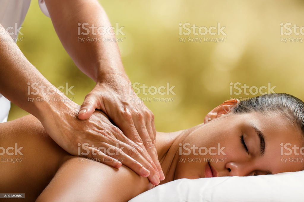Young woman enjoying massage in spa. stock photo