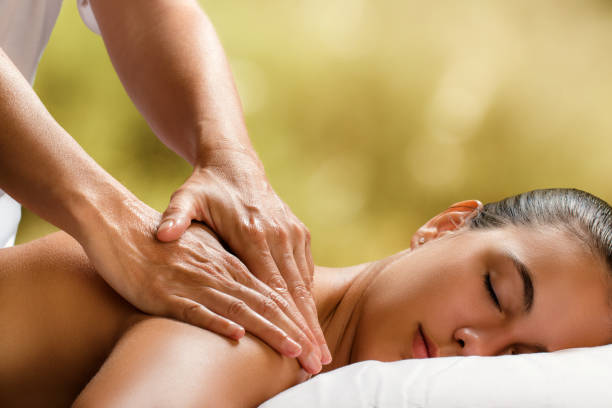 Young woman enjoying massage in spa. stock photo