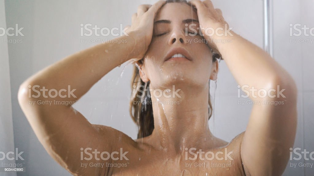 Closeup front view of young blond woman enjoying her morning shower....