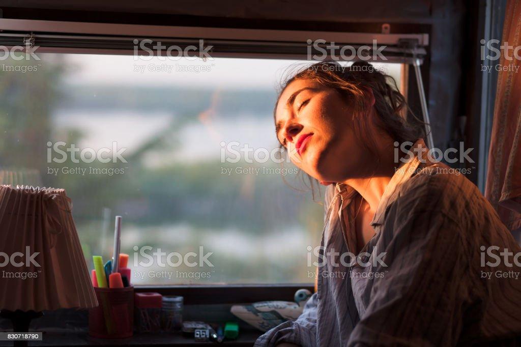 junge Frau, die Morgensonne neben ihrem Fenster genießen – Foto