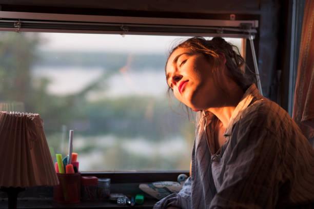 young woman enjoying morning sun next to her window - vitamin d стоковые фото и изображения