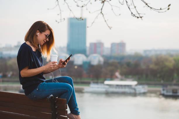jeune femme appréciant la musique sur le smartphone - écouteurs intra auriculaires photos et images de collection