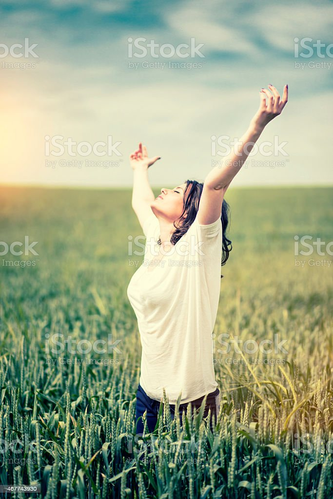 Young Woman Enjoying Nature with Spread Arms at Sunset stock photo
