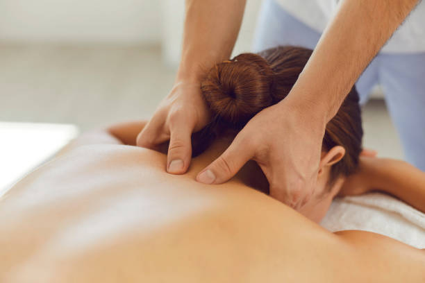 Young woman enjoying relaxing remedial body massage done by professional masseur stock photo