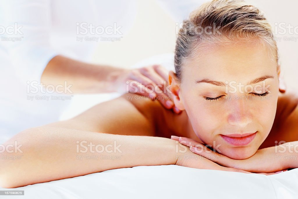 Young woman enjoying shoulder massage at spa royalty-free stock photo