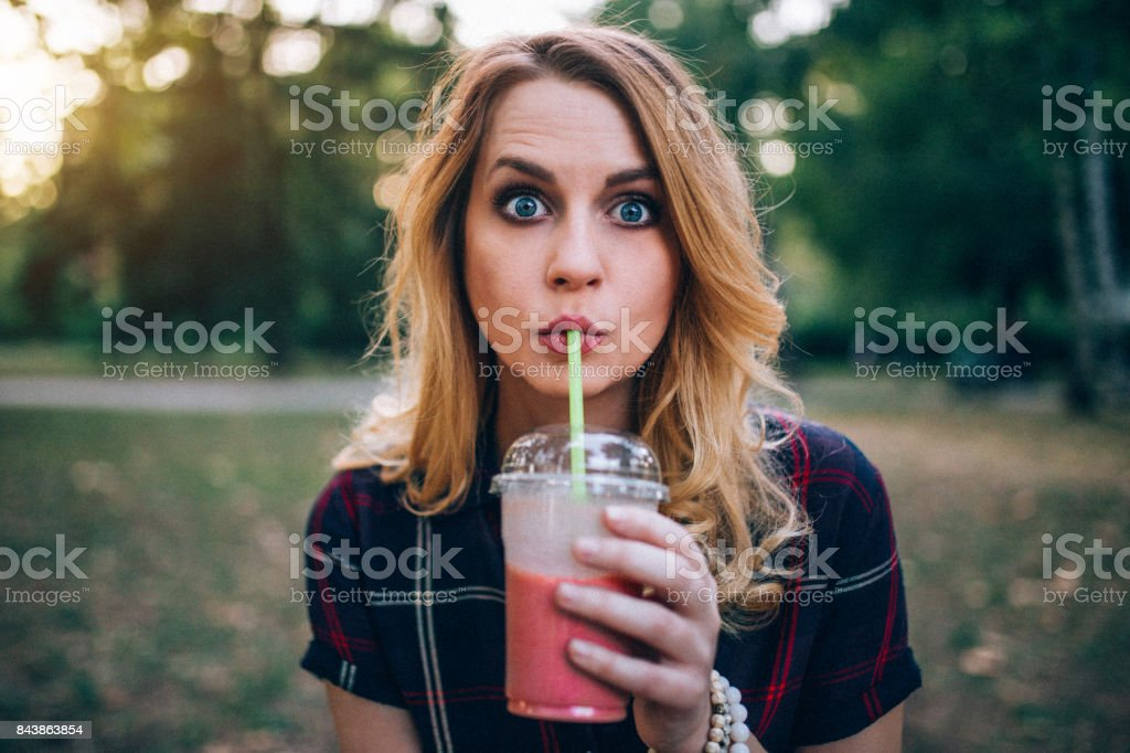 Young woman enjoying smoothie outdoors stock photo