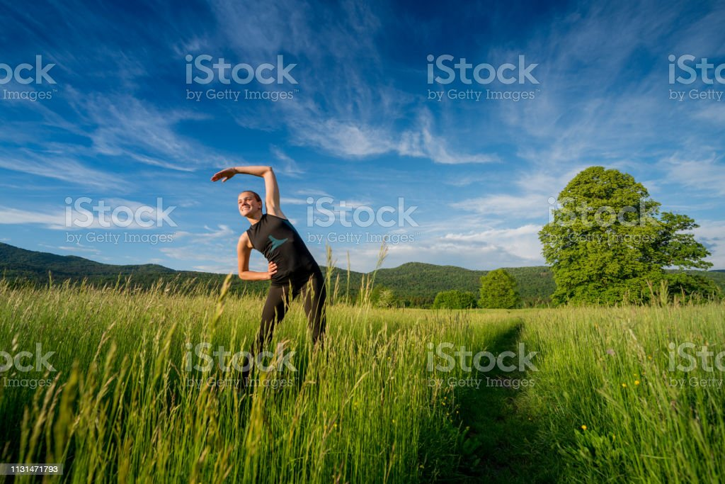 Young Woman Enjoying Stretching and Exercising in Nature in...