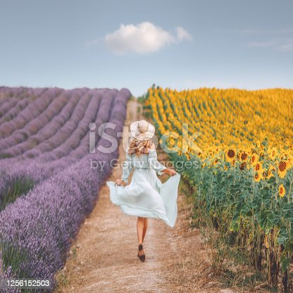 Rearview of joyful and happy young beautiful woman with white dress and hat walk on a road between lavenders and sunflowers fields on sunny day with cloudy blue sky in Valensole, Provence, France