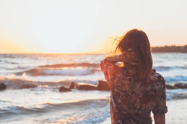 junge frau genießen sonnenuntergang und wellen am strand - haare ohne lockenstab wellen stock-fotos und bilder