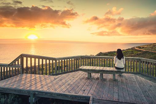 Young woman enjoying sunset at Hallett Cove boardwalk