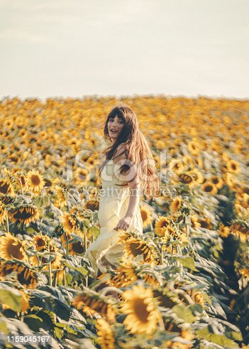 Young cute boho girl having fun with sun flowers in flower bed at beautiful and romantic summer sunset time scenery