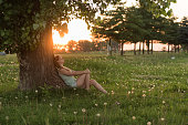 Young woman enjoying sunset under tree, thinking about future, relaxing, feeling free.