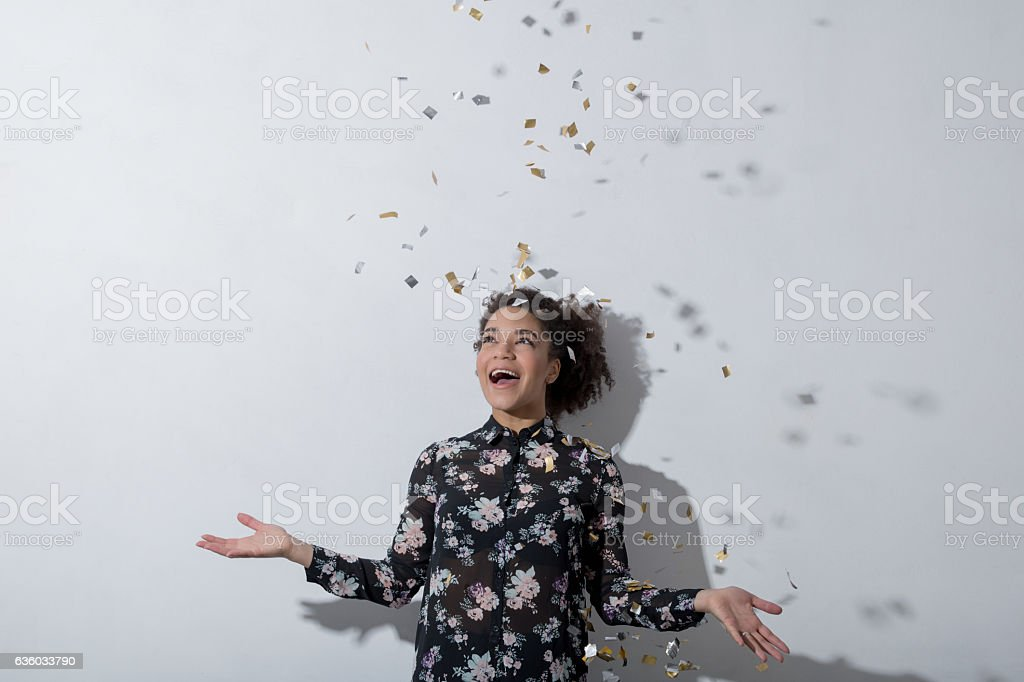 Young woman enjoying the party with confetti in air stock photo