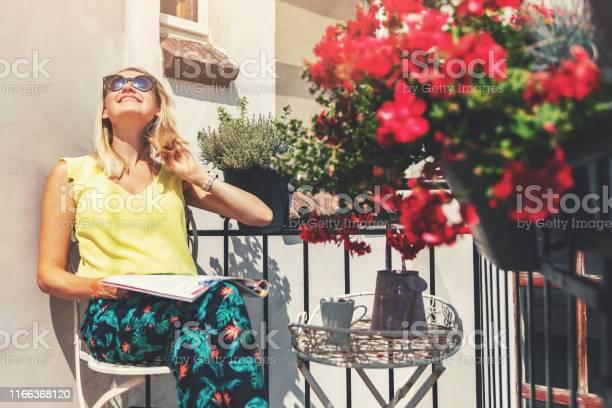Young woman enjoying the sun on romantic balcony with flower boxes picture id1166368120?b=1&k=6&m=1166368120&s=612x612&h=1iemdhots8ea38ldpzv80zpzoznp3cn zg6vfcuibno=