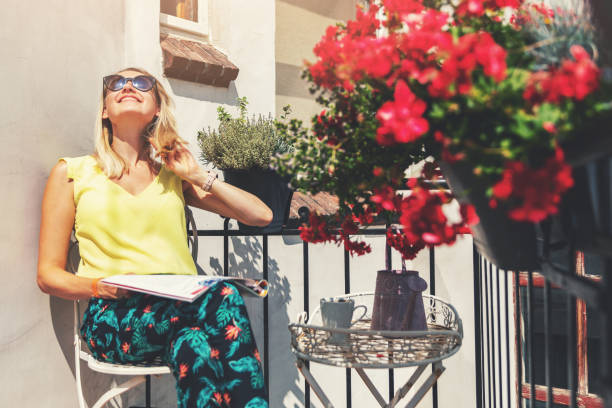 young woman enjoying the sun on romantic balcony with flower boxes stock photo