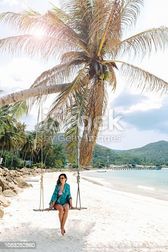 Pastel vintage toned image of a young brunette woman, enjoying her travel and vacation on the beautiful island of Koh Phangan, in the Gulf of Thailand. She is sitting on a swing by the palm tree, having a lazy day off.