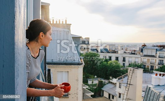 Vintage toned image of a young woman relaxing, drinking coffee, on the small balcony - window of her beautiful apartment on Montmartre, Paris. Taken in the magic hour just as the sun sets down over Parisian city scape in the background and the sunrays paint her hair bright.
