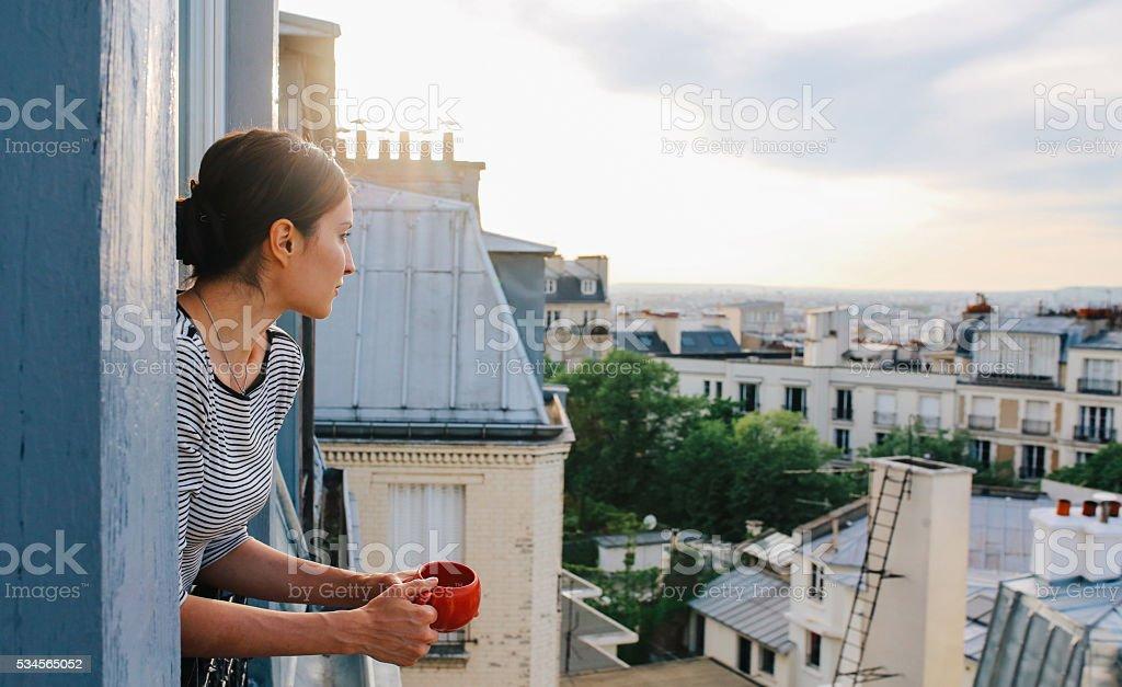 Jovem mulher desfrutando um vista de um apartamento parisiense - foto de acervo