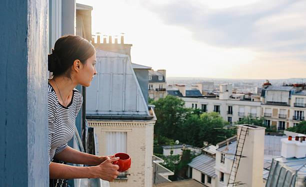 junge frau genießt die ansicht von einem pariser appartment - französische häuser stock-fotos und bilder