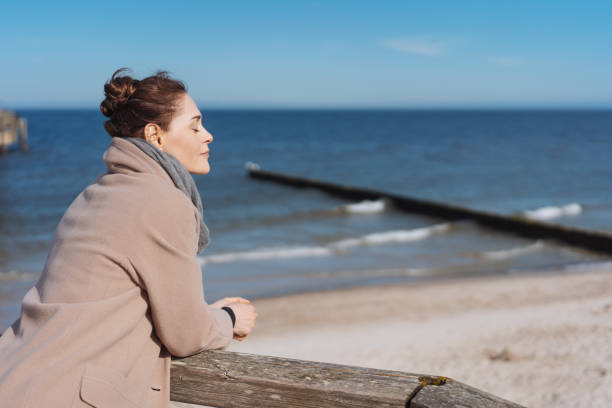Young woman enjoying the warm sunshine Young woman enjoying the warm sunshine at the seaside leaning on a wooden railing alongside the sea with closed eyes and a serene expression one mid adult woman only stock pictures, royalty-free photos & images