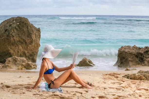 jonge vrouw genieten van tijd op het strand, tijdschrift lezen - newspaper beach stockfoto's en -beelden