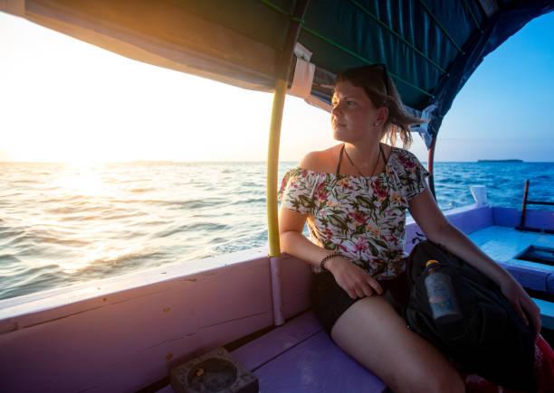 jonge vrouw genieten van reizen op boot - rondvaartboot stockfoto's en -beelden