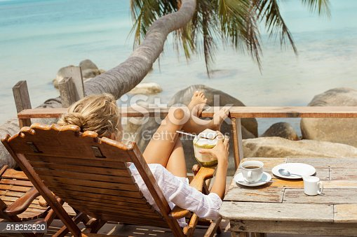 538041934 istock photo Young woman enjoys drinking coffee and coconut 518252520