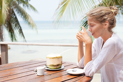 Young woman enjoys drinking coffee and coconut. Koh Phangan island, Thailand