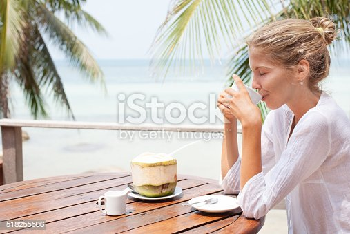 538041934 istock photo Young woman enjoys drinking coffee and coconut 518255506