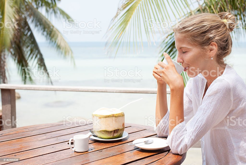 Young woman enjoys drinking coffee and coconut stock photo