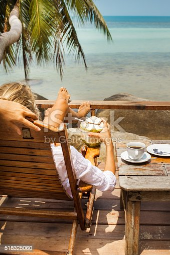 538041934 istock photo Young woman enjoys drinking coffee and coconut 518325060