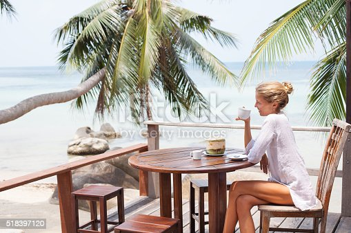 538041934 istock photo Young woman enjoys drinking coffee and coconut 518397120