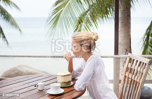 538041934 istock photo Young woman enjoys drinking coffee and coconut 518397258