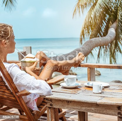 538041934 istock photo Young woman enjoys drinking coffee and coconut 530928238