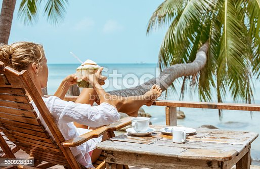 538041934 istock photo Young woman enjoys drinking coffee and coconut 530928332