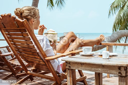 538041934 istock photo Young woman enjoys drinking coffee and coconut 530928420