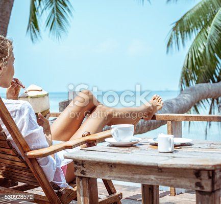 538041934 istock photo Young woman enjoys drinking coffee and coconut 530928572