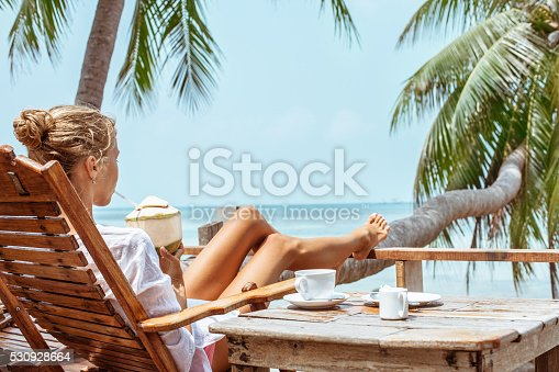538041934 istock photo Young woman enjoys drinking coffee and coconut 530928664